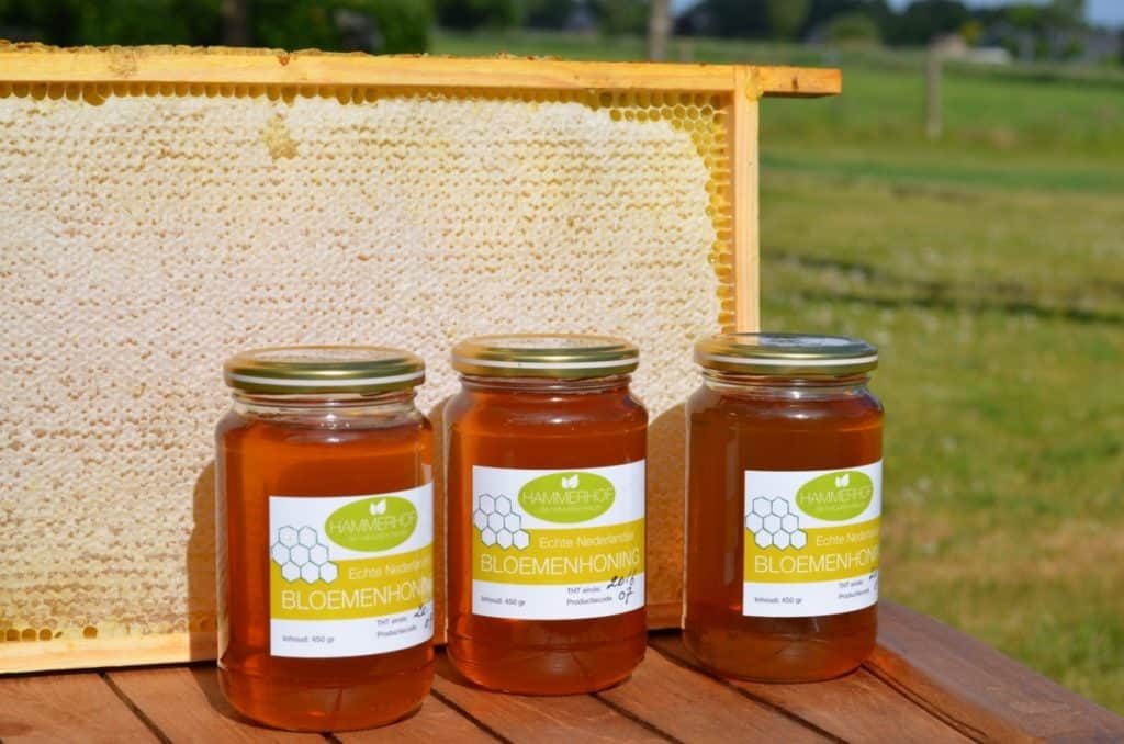 3 potten honing met een raampje vol honing op tafel