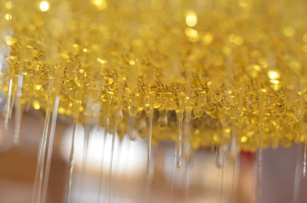 Druppels honing die uit een filter lekken