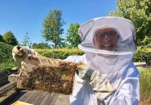 Lachende imker Ben met een raampje bijen