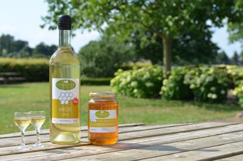 fles mede wijn met een pot honing en proefglaasjes