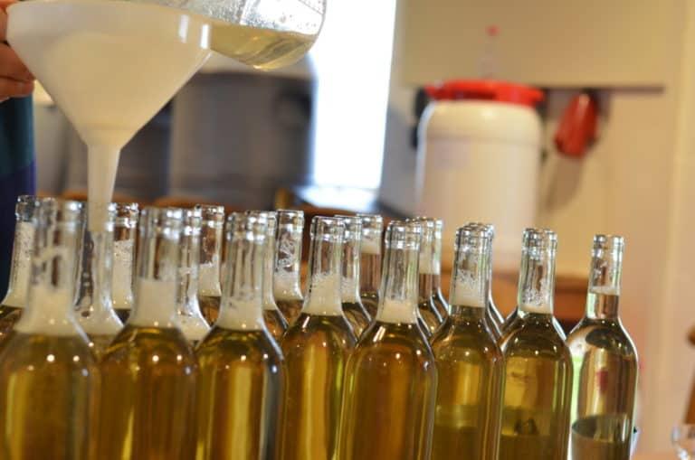 het vullen van wijnflessen met goudgele mede wijn